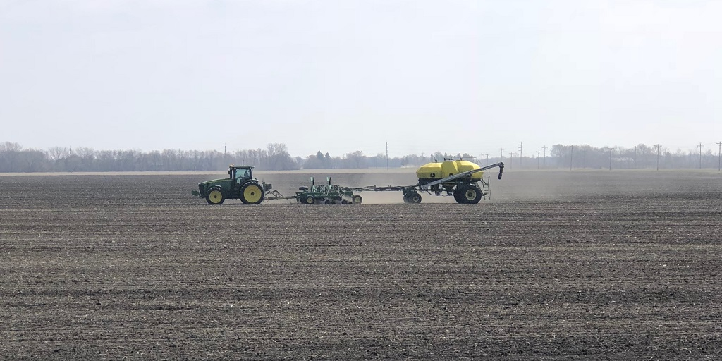 This agronomic image shows a tractor planting wheat.