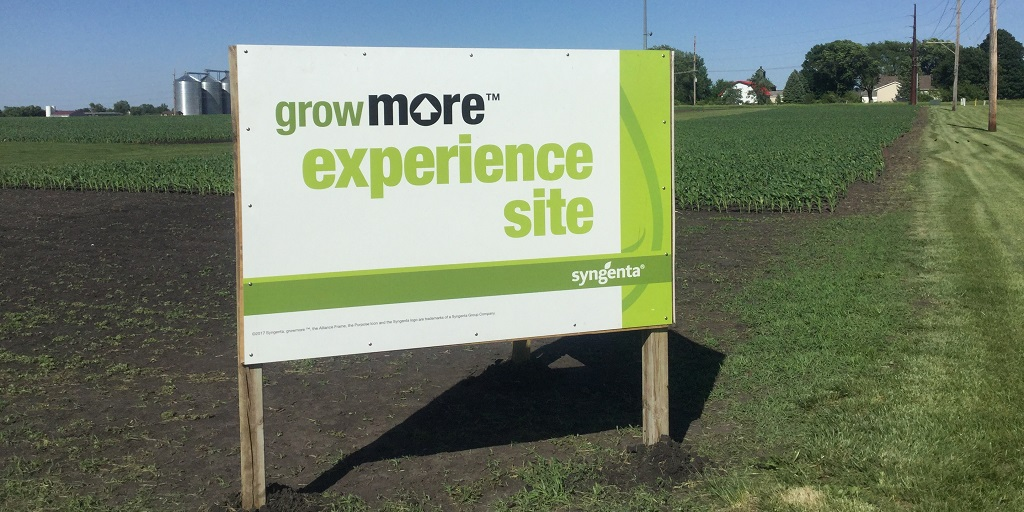 This image shows a Grow More Experience sign promoting field trials in Slater, Iowa.